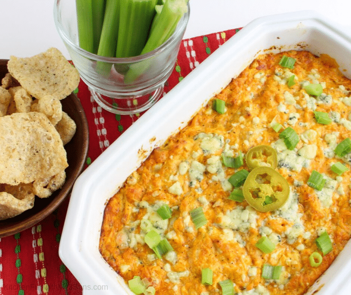 Baked easy buffalo chicken dip baked with pork rinds and celery beside dish