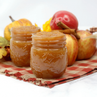 Mason jars filled with homemade applesauce sitting on a plaid napkin with fresh apples and cinnamon sticks