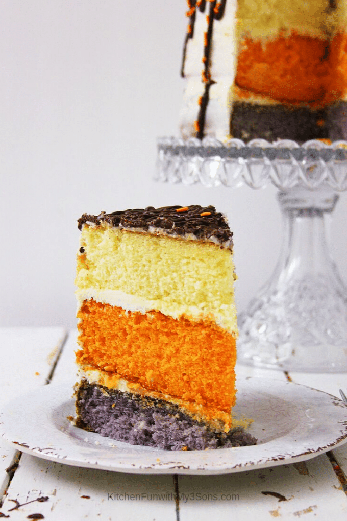 Pumpkin spice latte layer cake sitting on a glass cake stand with one slice taken out and on a plate
