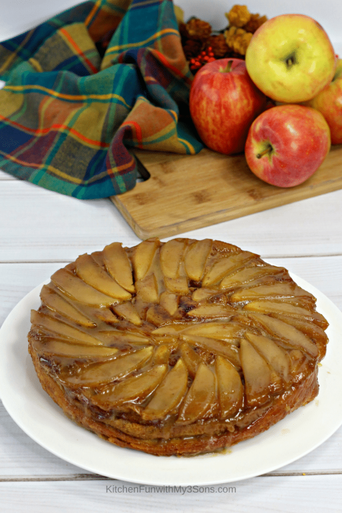 A cinnamon roll apple upside down cake on a white serving platter with apples in the background