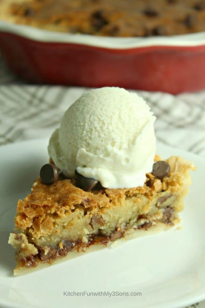 A single slice of chocolate chip pie on a white saucer with ice cream on top