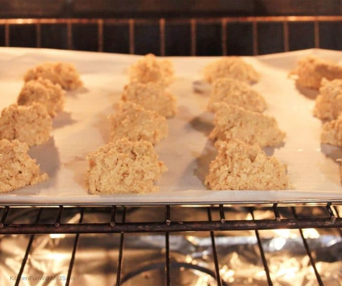 Baking sheet filled with pumpkin spice sugar cookies in an oven