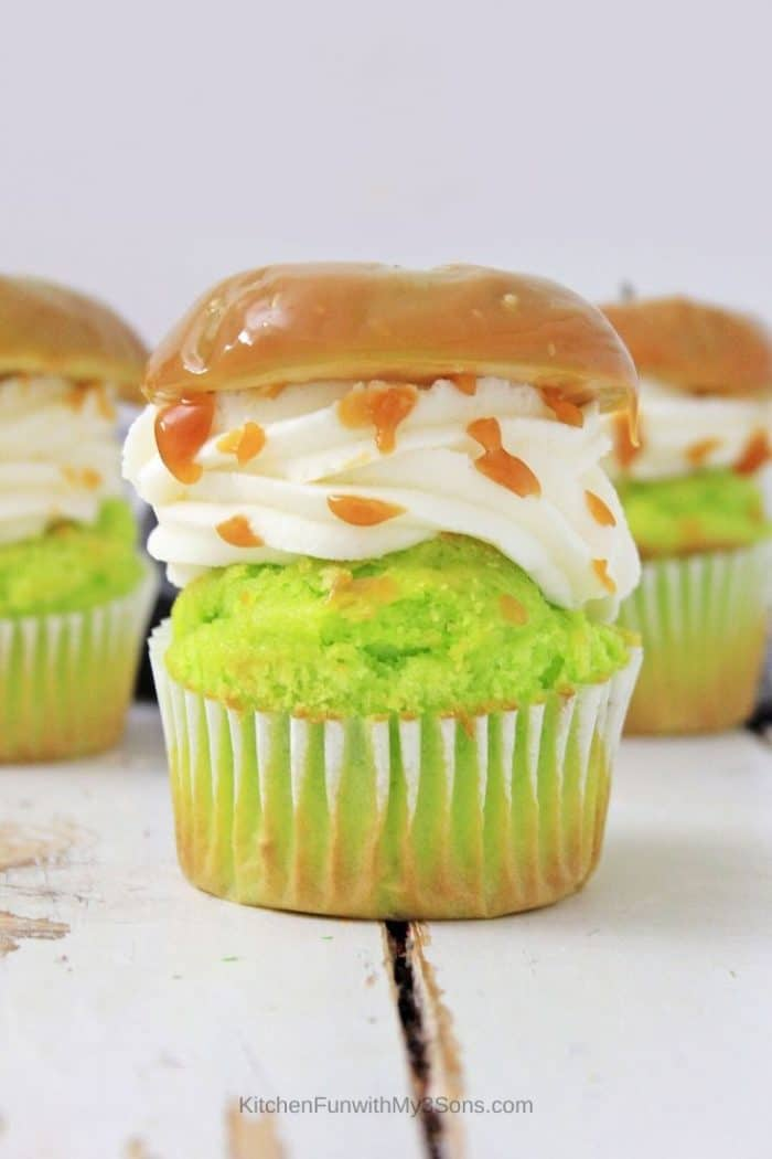 Caramel apple cupcakes in a row on a white wooden surface