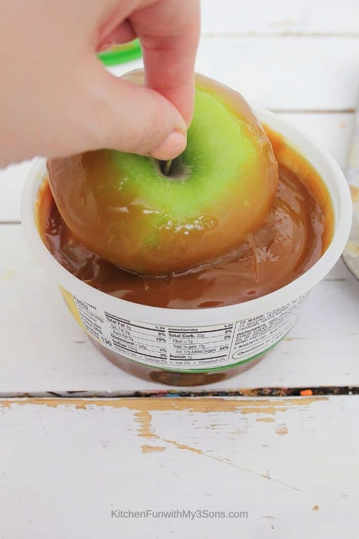 Dipping apples into caramel dip for cupcakes