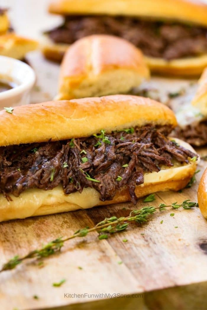 French dip sandwiches ready to eat and laying on a wooden cutting board
