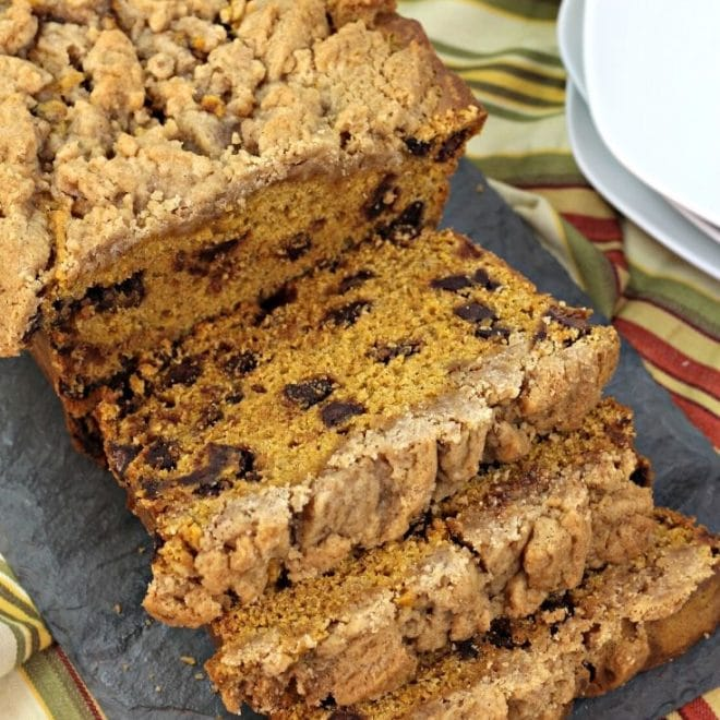 Overhead picture of a sliced loaf of pumpkin streusel bread on a gray napkin with plates in background