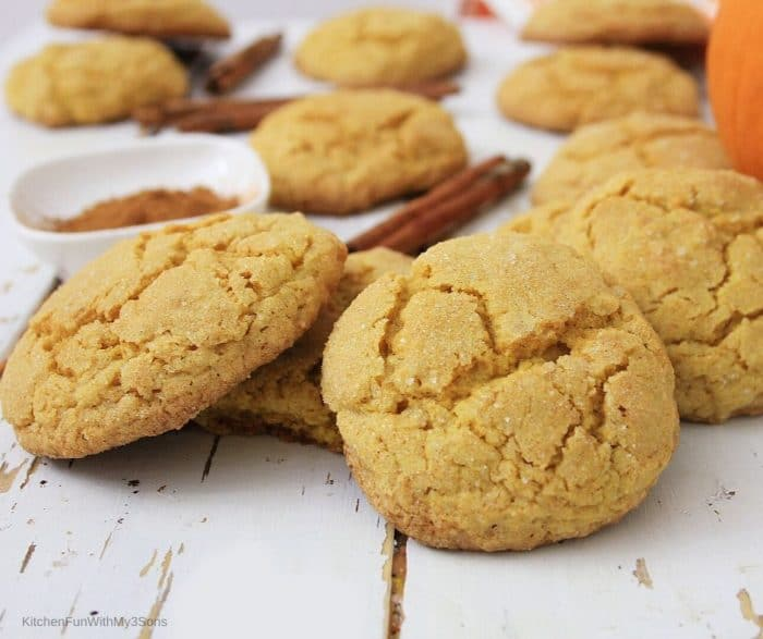 Pumpkin sugar cookies laying on a wooden surface with cinnamon sticks in background
