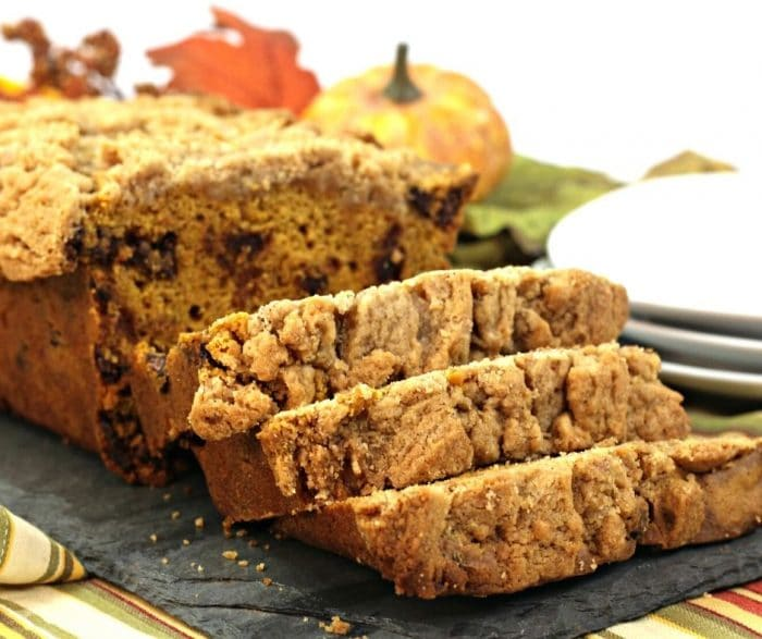 Slices of pumpkin streusel bread with chcoolate chips laying on a gray cloth with fall decor in background