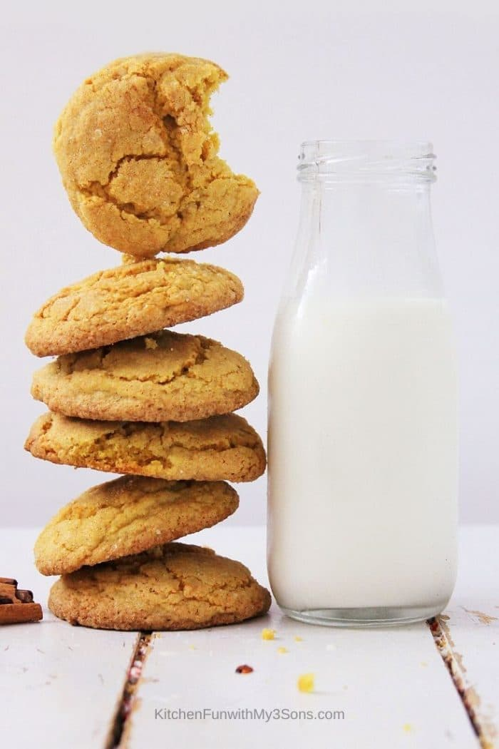 Tall stack of pumpkin sugar cookies next to a bottle of milk
