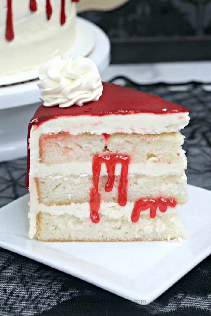 Up close picture of a slice of iced vampire cake sitting on a white cake stand