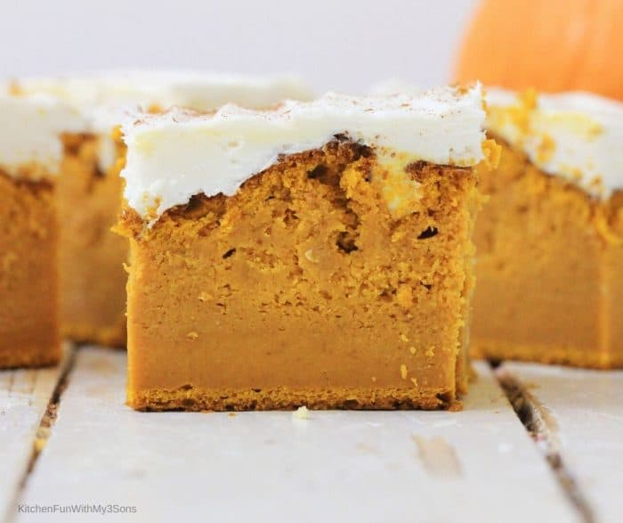 Up close picture of a sliced pumpkin bar topped with cream cheese frosting