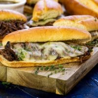Up close picture of french dip sandwiches on a cutting board ready to serve