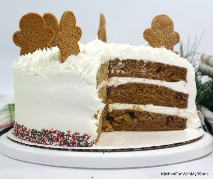 Gingerbread layer cake on a white cake stand topped with gingerbread cookies