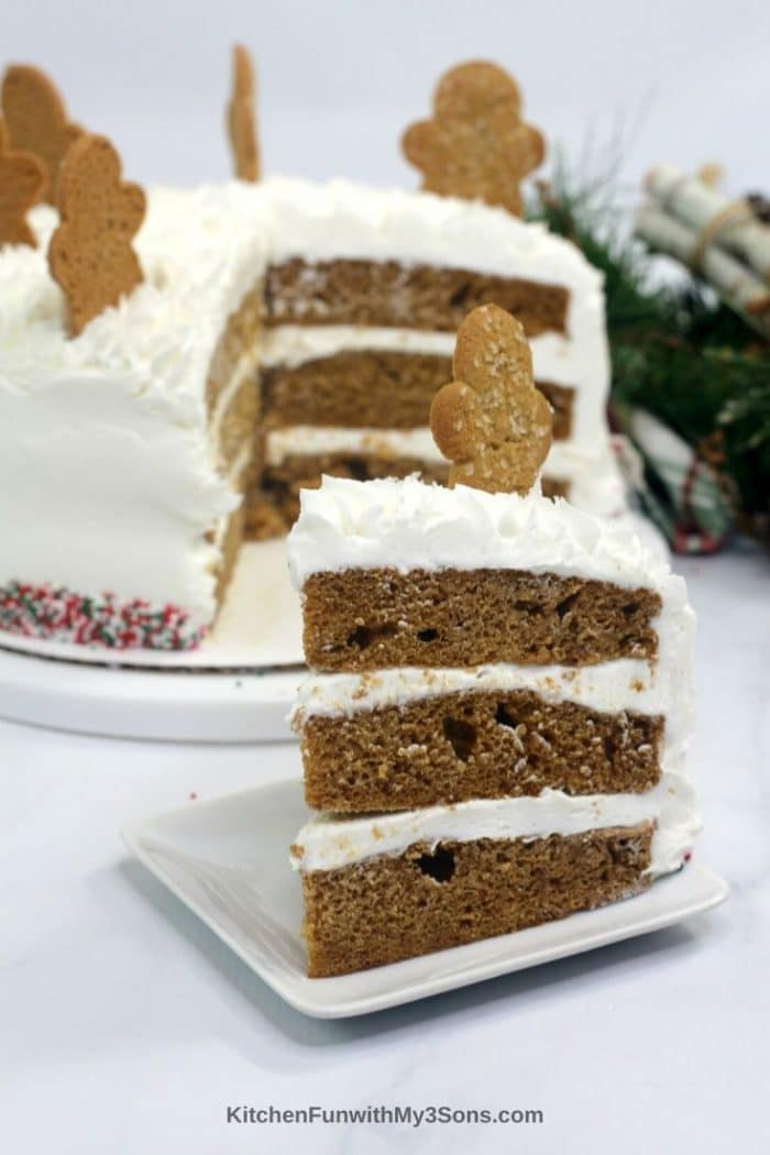 Gingerbread layer cake on a white plate on white table topped with cookie