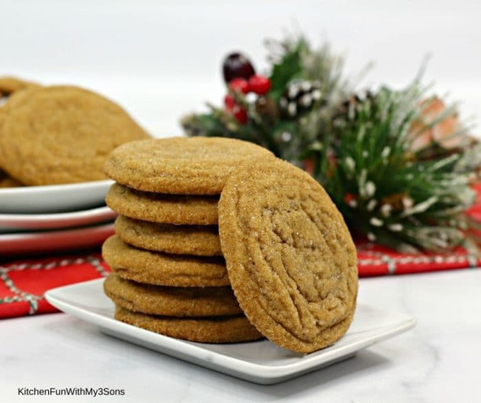 Soft Molasses cookies stacked on a plate in front of holiday decorations