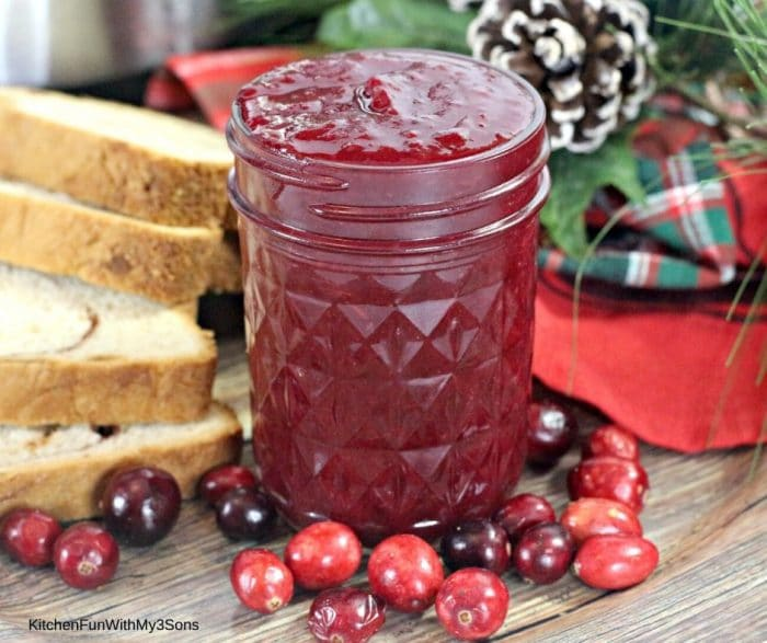Sliced bread next to a jar of cranberry butter with fresh cranberries on the table