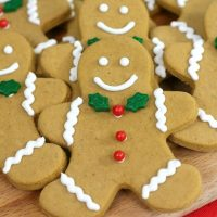 Up close picture of a gingerbread man cookie with green leaf tie and red berry buttons