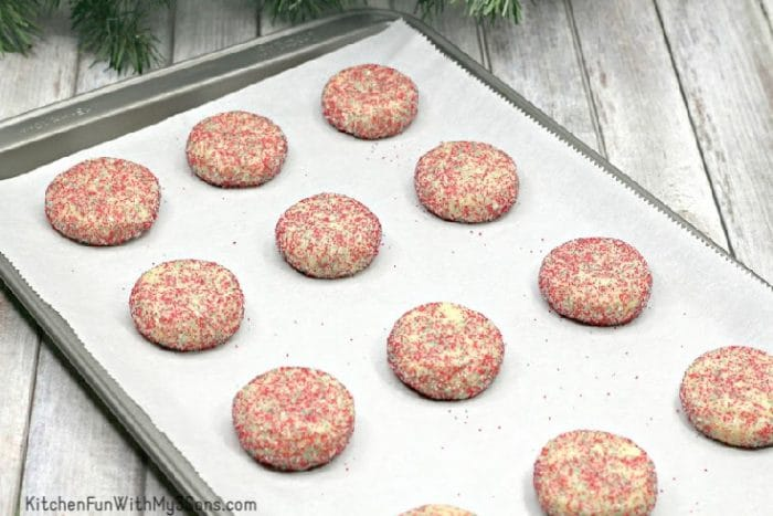 Christmas sugar cookies with sprinkles on baking sheet