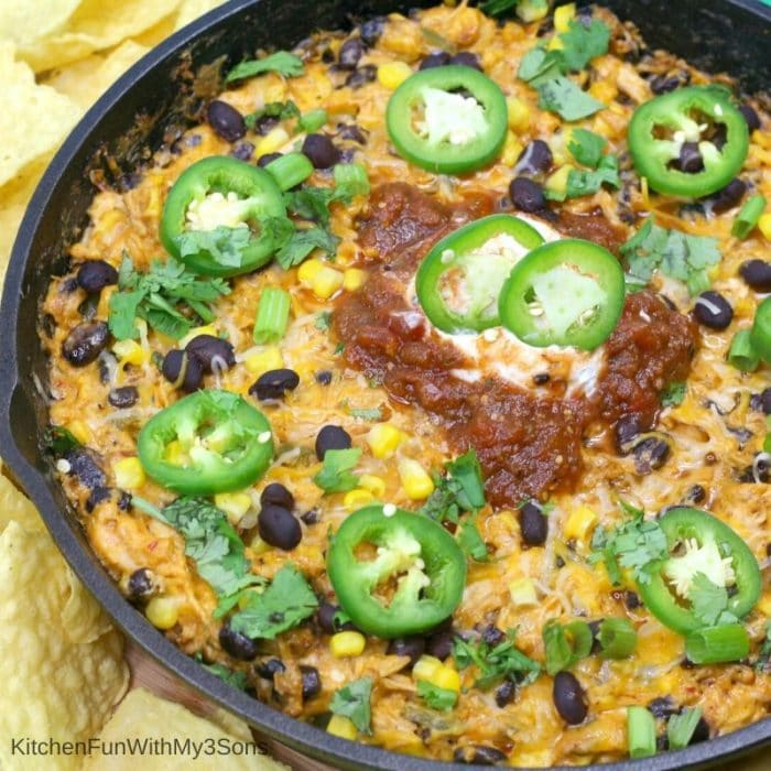 Overhead up close square picture of chicken enchilada dip in a cast iron skillet