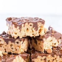 Stack of chocolate caramel oat cereal bars on a white platter
