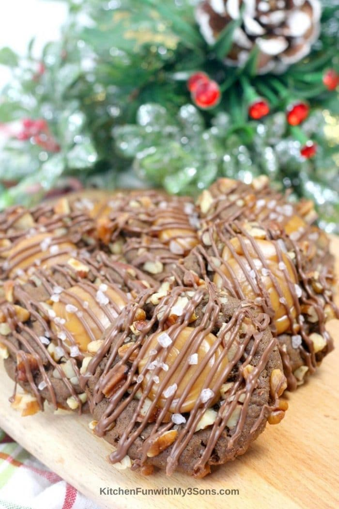 Stacked turtle cookies with pecans and drizzled chocolate on top