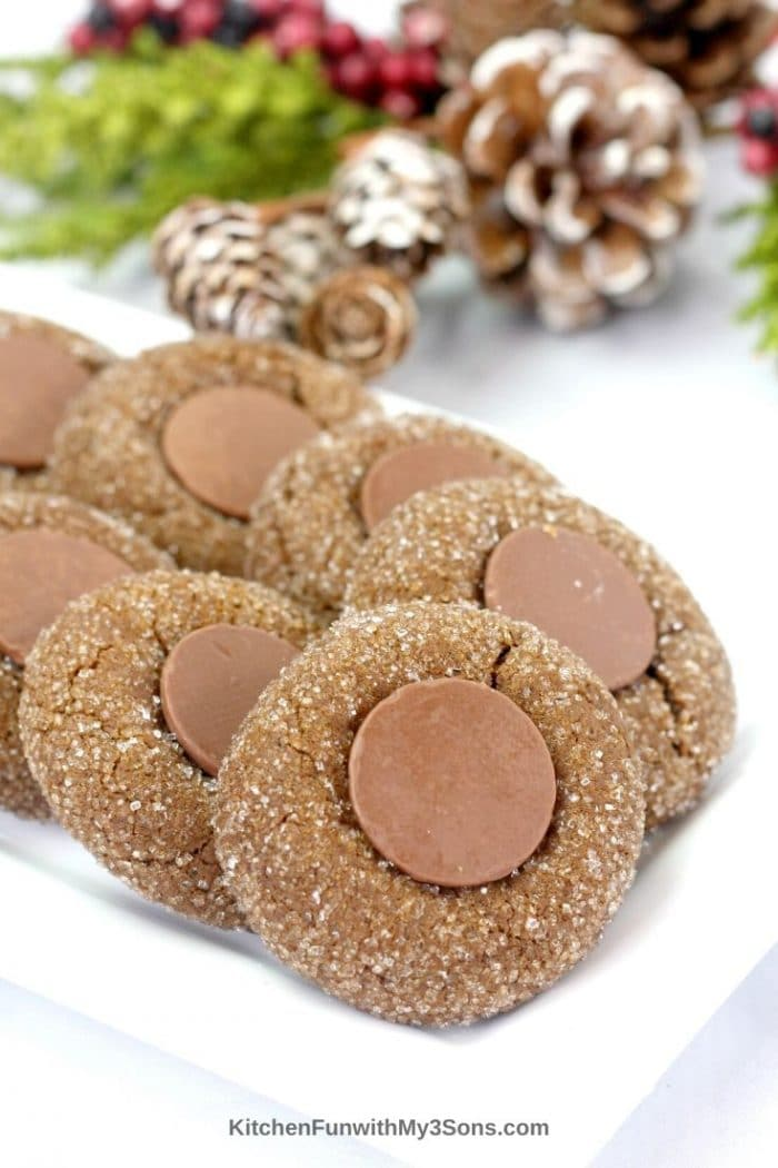 Stacks of gingerbread cookies on a platter with holiday decorations in the background