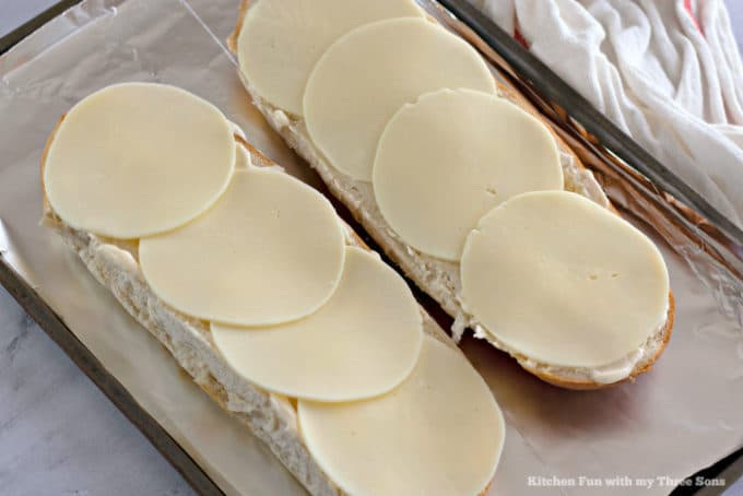 Italian bread topped with mayonnaise and provolone cheese slices