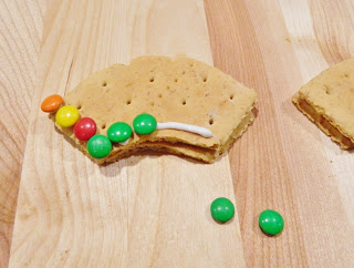 Squeeze on white cookie frosting on the top of one graham cut out in a line and add on the different colored mini M&M's