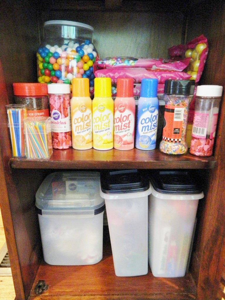 This is the bottom section of the cabinet filled with more sprinkles, gum balls, colored sticks, edible markers, & candy