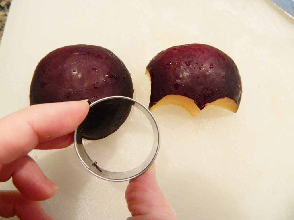 Place one plum on a plate. Cut the other plum in half