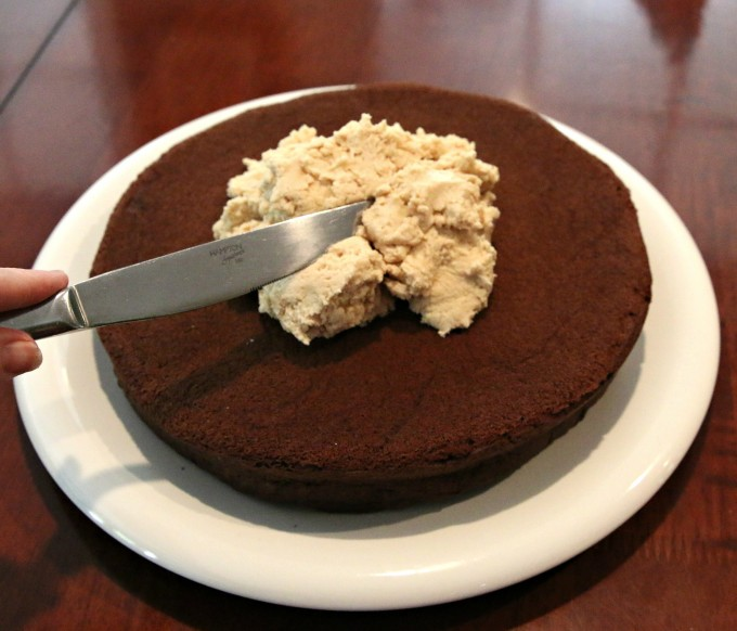 Spreading peanut butter filling over chocolate cake