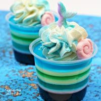 These Mermaid Jello Shots will be such a fun addition to your next party. Layered with colorful coconut rum jello and topped with a homemade whipped cream.