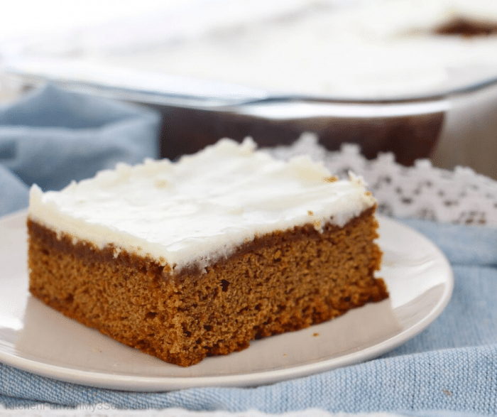 A slice of apple butter apple cake recipe on a white plate with icing on top that is sitting on a blue cloth