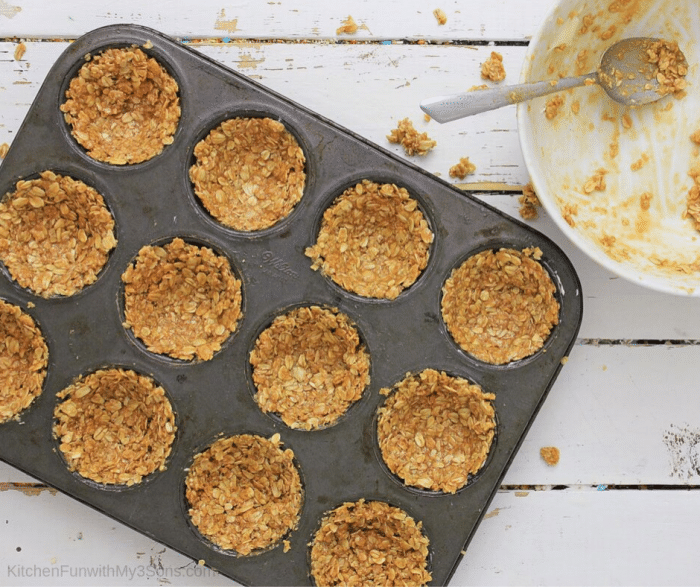 Adding granola to muffin tins to make baked oatmeal cups