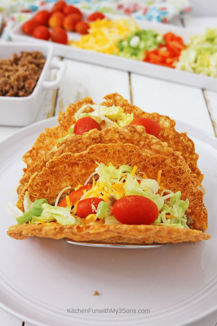 Keto taco shells filled with veggies and meat sitting on a white plate with toppings in background
