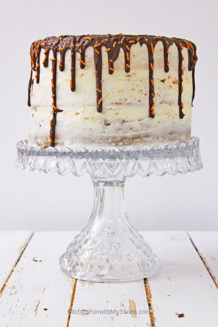 Pumpkin spice latte layer cake sitting on a glass cake stand with one slice taken out and on a plate (1)