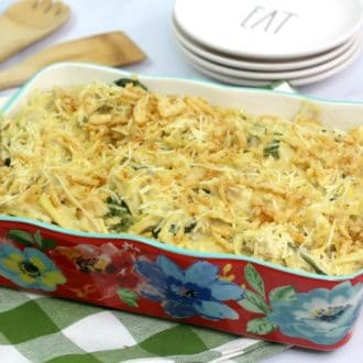 A floral baking dish filled with chicken spaghetti casserole sitting on a green plaid napkin
