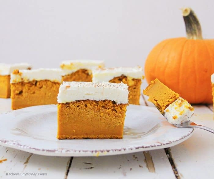 A pumpkin bar with cream cheese on a white plate with a fork full of bar