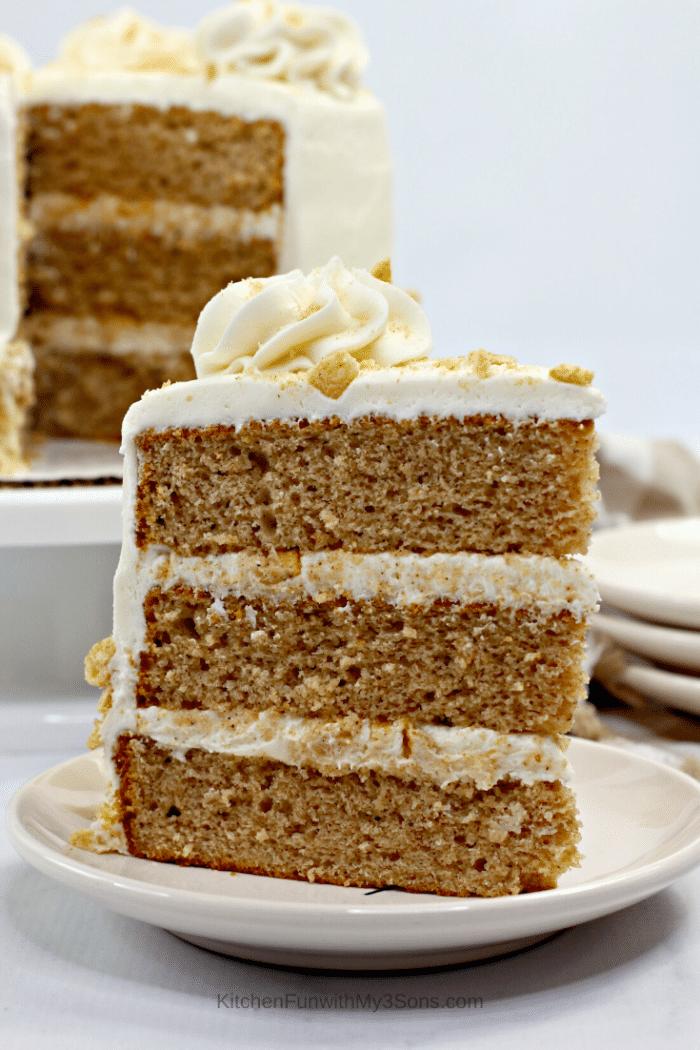 A slice of cinnamon toast crunch cake in front of the remaining whole cake