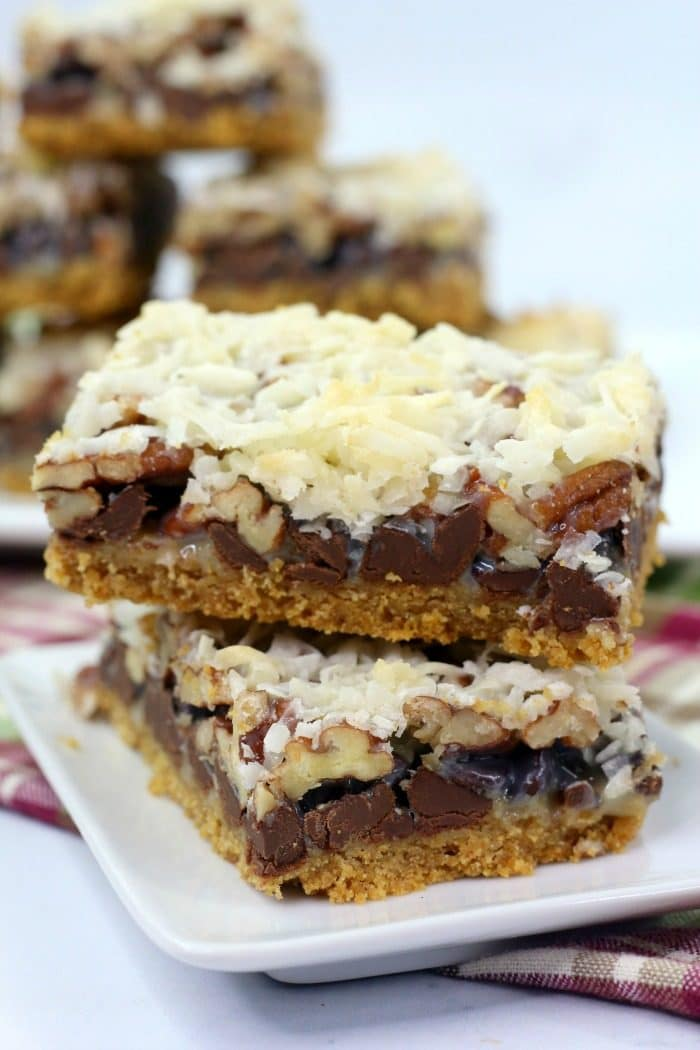 A stack of hello dolly bars on a white plate topped with coconut