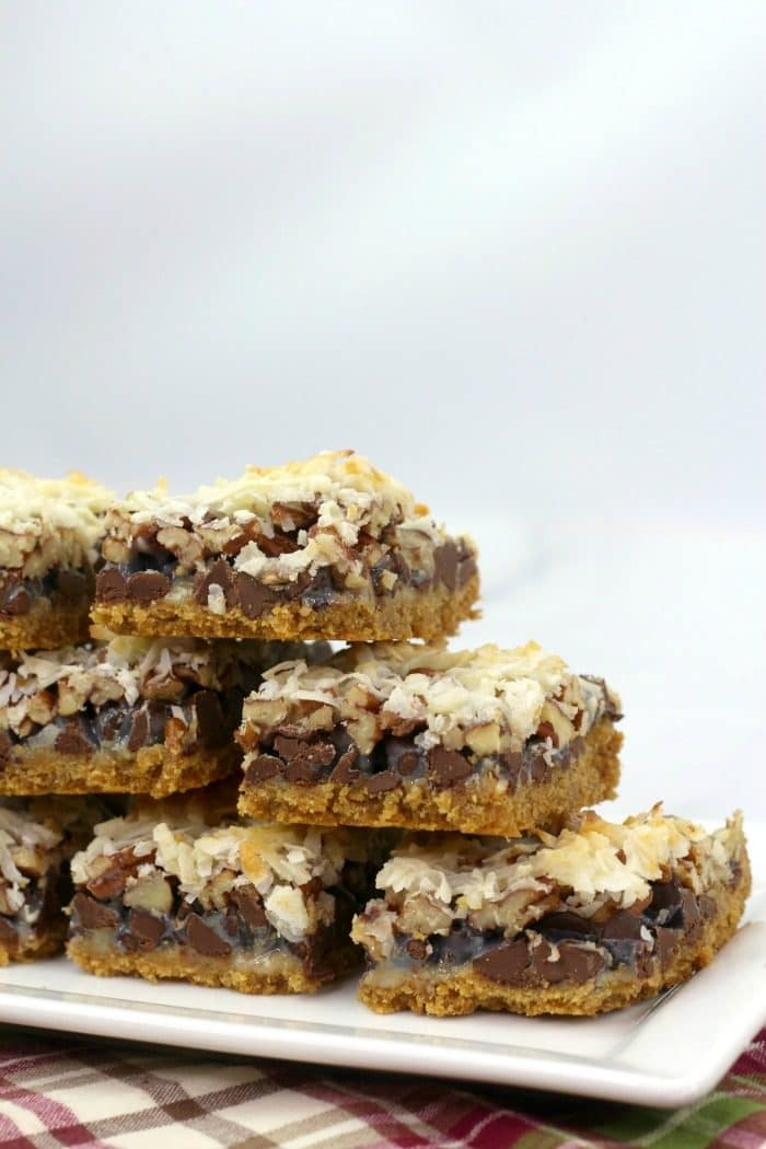 Large stack of hello dolly cookie bars on a large white serving platter
