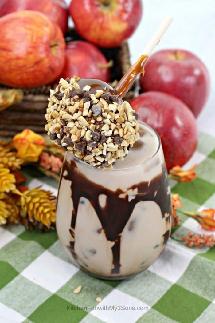 Overhead picture of a chocolate caramel apple cocktail topped with a small caramel apple covered in nuts