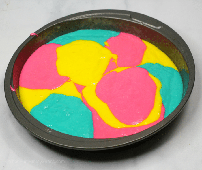Overhead picture of cake batter marbled with tie dye colors in a round pan