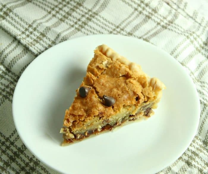 Overhead up close picture of chocolate chip pie on white plate sitting on striped towel