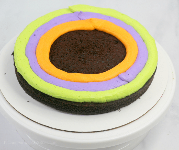 Preparing a chocolate layer cake with colorful icing on a cake stand