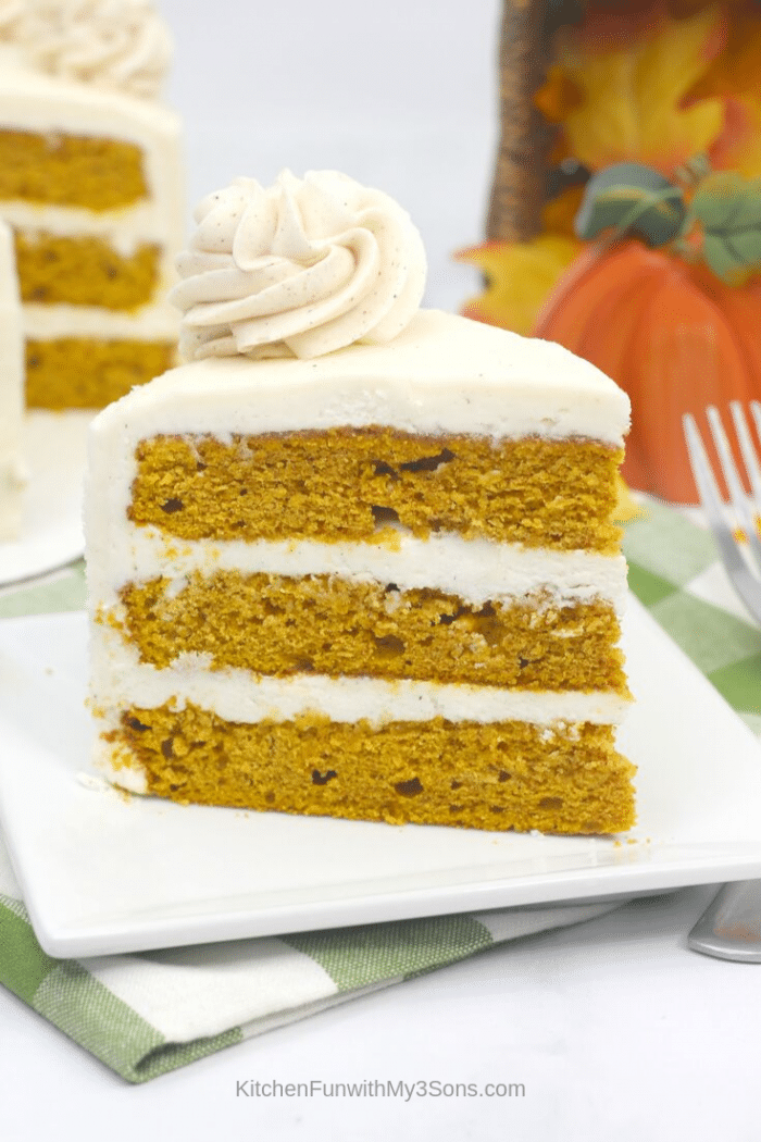 Single slice of pumpkin cake recipe with cream cheese icing on a white plate