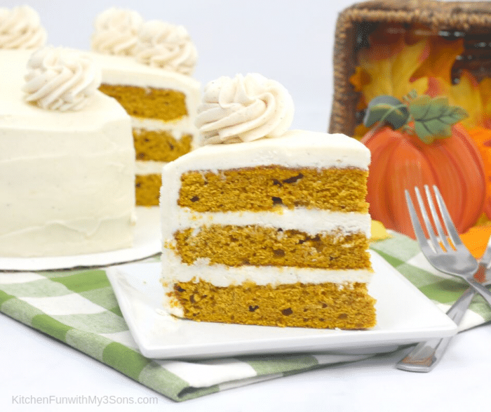 Slice of pumpkin cake recipe sitting on a white plate on green plaid napkin