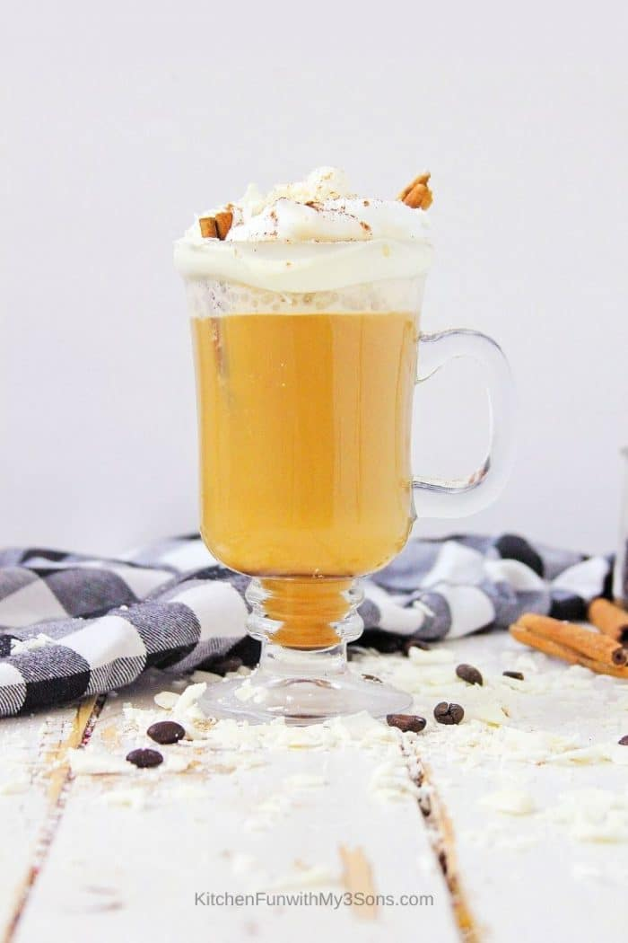 Tall glass of pumpkin spice latte topped with whipped cream