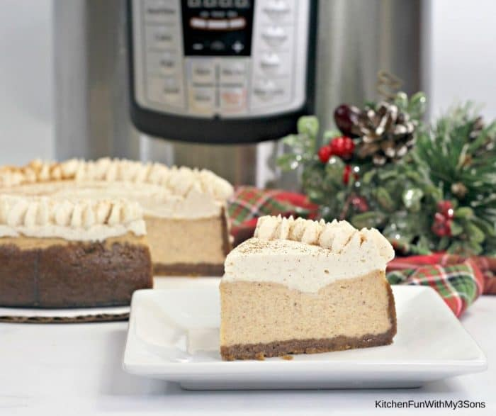 A slice of eggnog cheesecake on a white plate in front of instant pot