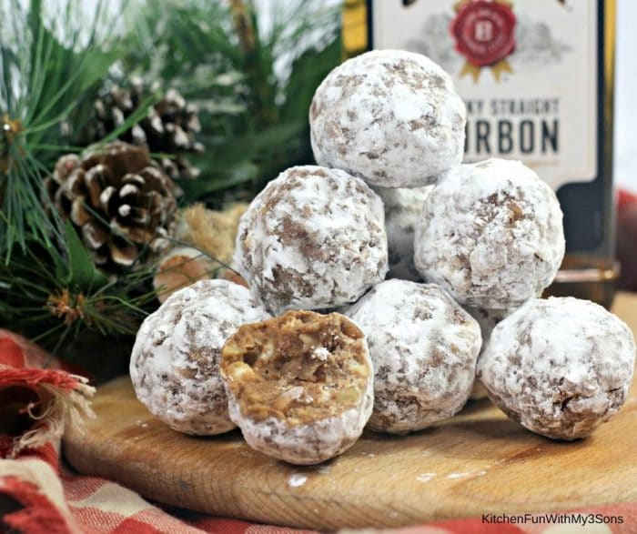 Bourbon balls stacked on a wooden platter in front of holiday decor